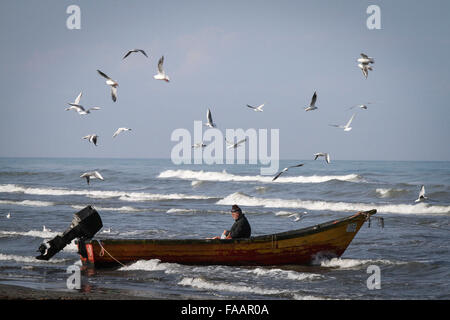 Anzali Port, Iran. 24th Dec, 2015. A boatman waits for passenger as he sits at his boat on the beach of Anzali Port - Stock Photo