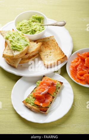 toasts with salmon and avocado, food closeup - Stock Photo