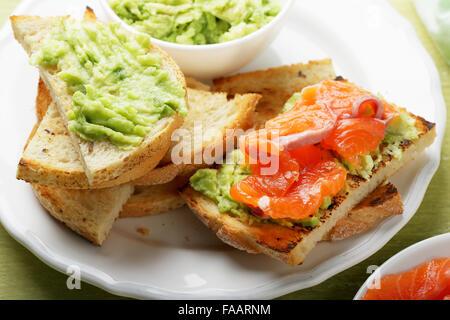 bruschetta with salmon and avocado sauce, food closeup - Stock Photo