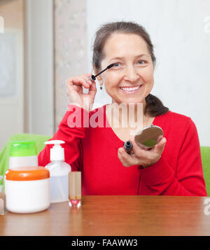 Smiling mature  woman in red mascaras her eye-lashes in home - Stock Photo