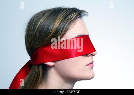 MODEL RELEASED. Woman wearing red blindfold. - Stock Photo