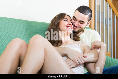 Young loving man tenderly embracing girlfriend on sofa in the living room - Stock Photo