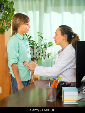 Female doctor examining stomach of teenage boy in clinic - Stock Photo
