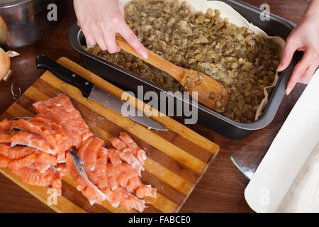 Closeup of cooking fish pie with salmon and eggplants in baking sheet - Stock Photo