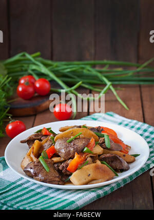 Roast chicken liver with vegetables on wooden background - Stock Photo