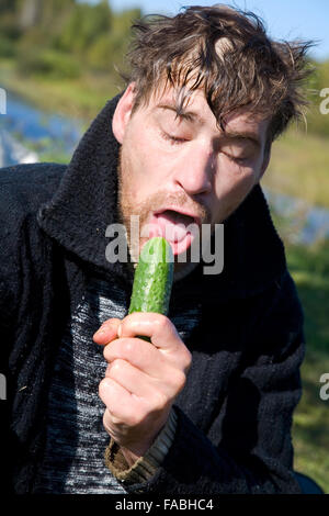 tramp eats green cucumber - Stock Photo