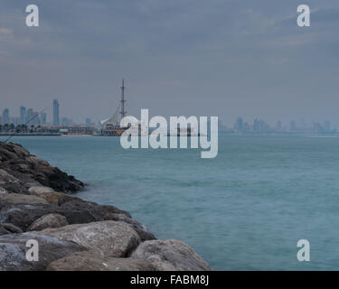 Looking across to Kuwait City as sunset approaches, with Maki restaurant in the foreground - Stock Photo