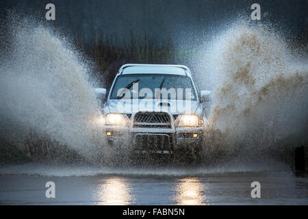 Driving through floodwater on a country road in North Yorkshire in the United Kingdom. - Stock Photo