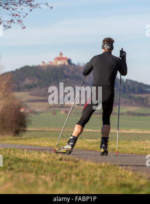 Holzhausen, Germany. 26th Dec, 2015. A man stands on sky rollers as he travels through spring-like landscape during - Stock Photo