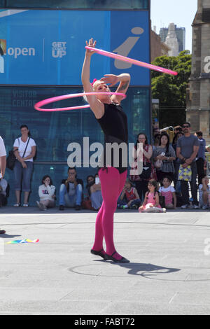 Street performer showing a hula-hoop performance on Federation Square in Melbourne, Victoria, Australia, on a sunny - Stock Photo