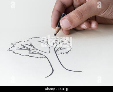 A child drawing a tree with a very short pencil stub expressing he concept of the conservation of the Earth's Resources - Stock Photo