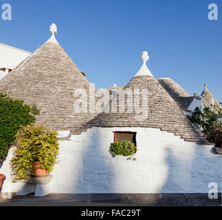 Typical trulli buildings with conical roofs in Alberobello, Apulia, Italy - Stock Photo