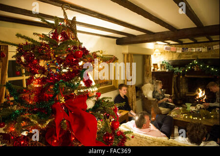 A Warm Family Scene On Christmas Day With Tree In Country Cottage