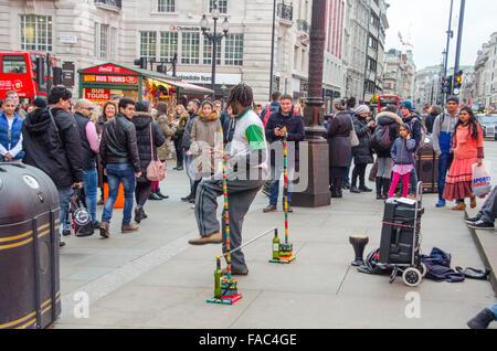 London, UK, 26 December 2015, Street entertainer, limbo dancer, busking.   Boxing day shopping in Oxford Street - Stock Photo