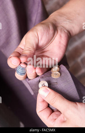 The dressmaker sews a button on a jacket - Stock Photo
