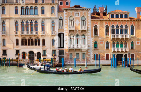 Tourists in venetian gondola in Grand Canal, historic buildings in the background, Venice, Italy - Stock Photo