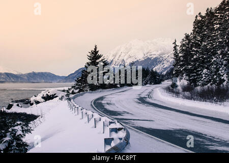 Plowed road in Southeast Alaska near Haines with snow in evening light. - Stock Photo