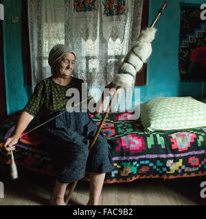 elderly woman while spinning wool in the district of Maramures, Romania - Stock Photo