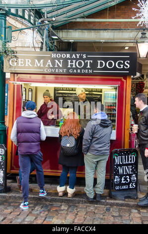London, UK, 24 December 2015, German hot dog and mulled wine stand in Covent Garden Market plazza  in the West End. - Stock Photo