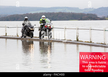 Bikers travel through flood waters on the road at Storth on the Kent Estuary in Cumbria, UK, during the January - Stock Photo