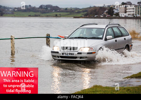 A motorist travels through flood waters on the road at Storth on the Kent Estuary in Cumbria, UK, during the January - Stock Photo