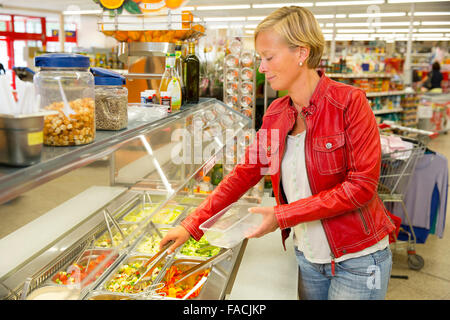 Woman in a supermarket at the salad bar - Stock Photo