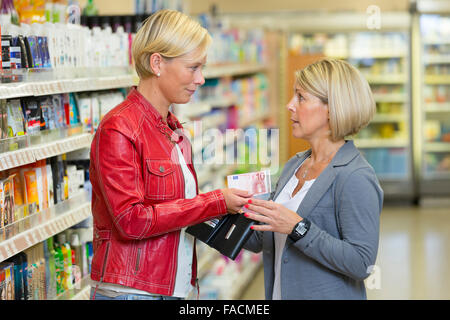 Woman borrows her friend money at the supermarket - Stock Photo