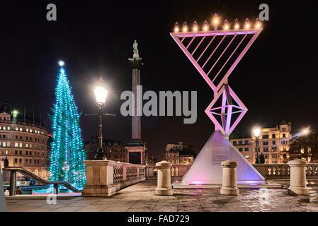 LONDON, UK - DECEMBER 19: Night shot of Menorah next to Christmas tree in Trafalgar Square, set up for Chanukah. - Stock Photo