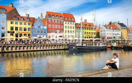 Copenhagen, Denmark - woman relaxing at Nyhavn Canal - Stock Photo