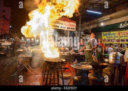 Crazy chef cooking morning glory with massive flames in Chinatown in Bangkok, Thailand - Stock Photo