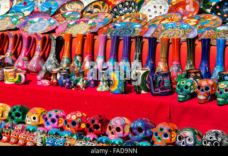Traditional brightly coloured Mexican ceramics including sugar skulls,on sale with a red tablecloth in Yucatan, - Stock Photo