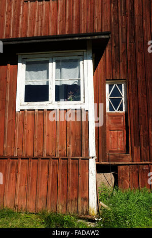red wooden Finnish house, white window, green grass - Stock Photo