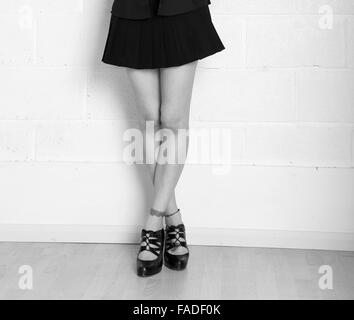Long legs and a short skirt on a fashion model in the studio. - Stock Photo