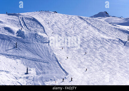 Ski slope on Hinterux glacier in Austrian Alps with skiers, snowboarders and snow lances. - Stock Photo