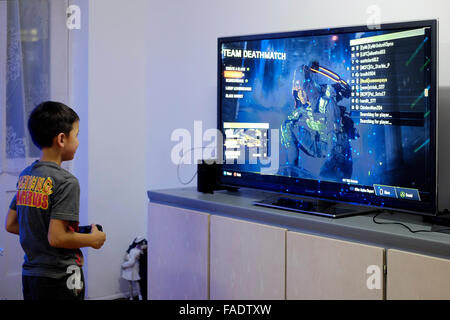 young boy playing video game on big flat screen tv in england uk - Stock Photo