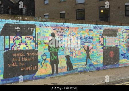 Multi-coloured brick wall with life captions, black stencils shop kiosks, child running, man standing, Wheler Street, - Stock Photo