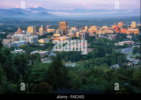 Sunrise lights the buildings of downtown Asheville, North Carolina, nestled in the Blue Ridge Mountains. USA. - Stock Photo
