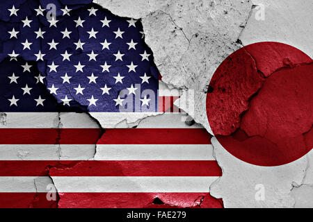 flags of USA and Japan painted on cracked wall - Stock Photo