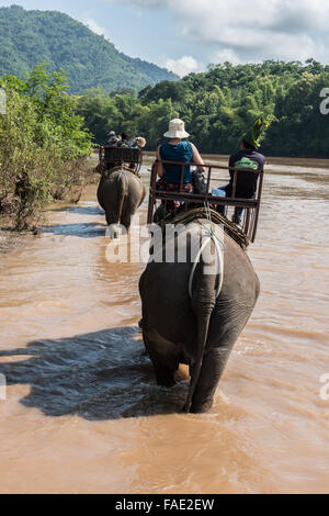 Tourists travelling on top of elephants on Nam Khan river in Luang Prabang province of Laos. Travelling on elephants - Stock Photo