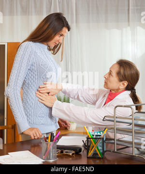 Female doctor in uniform examining stomach of teen girl patient - Stock Photo
