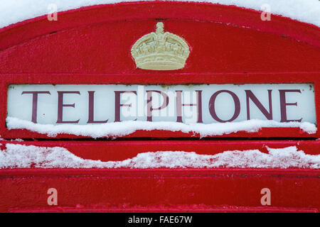 Old fashioned red telephone box in the snow, UK - Stock Photo