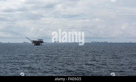 Many offshore oil rigs on the horizon off the coast of Brunei Darussalam, South China Sea. Cloudy sky. - Stock Photo