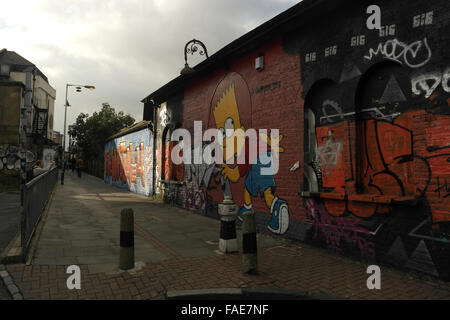 Grey sky view Pedley Street towards Brick Lane with scrawl and Graffiti Life image Bart Simpson painted wall, London, - Stock Photo