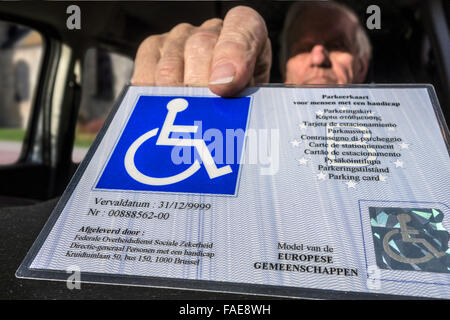Handicapped elderly man placing EU parking card for people with disabilities – Blue Badge - behind windscreen of - Stock Photo