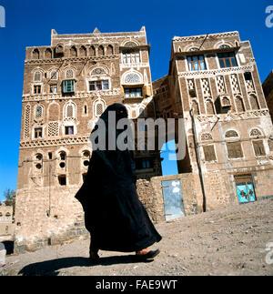 A veiled Muslim woman walks on a Sanaa street, Yemen.At background typical Yemen houses. - Stock Photo