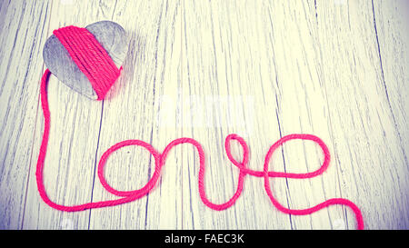 Vintage toned wooden heart with love sign. - Stock Photo