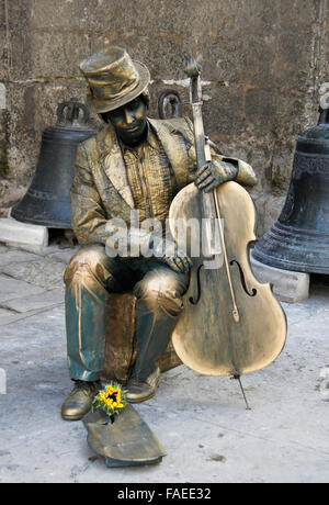 Street performer dressed as bronze statue with cello, outside church of San Francisco de Asis, Habana Vieja (Old - Stock Photo