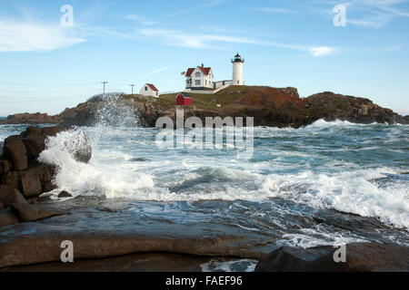 High tide surrounds the nubble island of Cape Neddick lighthouse in southern Maine as waves break over rocky coast. - Stock Photo