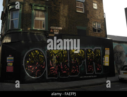 Colourful 'Orfn' graffiti painted on black wall boards, next to mural of Charlie Burns, Bacon Street at Brick Lane, London, UK