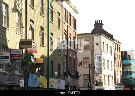 White sky sunny day oblique view of Brick Lane to Cheshire Street with six 'To Let' rental signs on buildings, London - Stock Photo